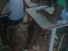 Alunos em sala de aula com assoalho alagado