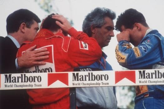 Os pilotos da Ferrari, Nicola Larini, e da Benetton, Michael Schumacher, choram ao saber da morte de Senna. FOTO: CLAUDIO LUFFOLI/AP